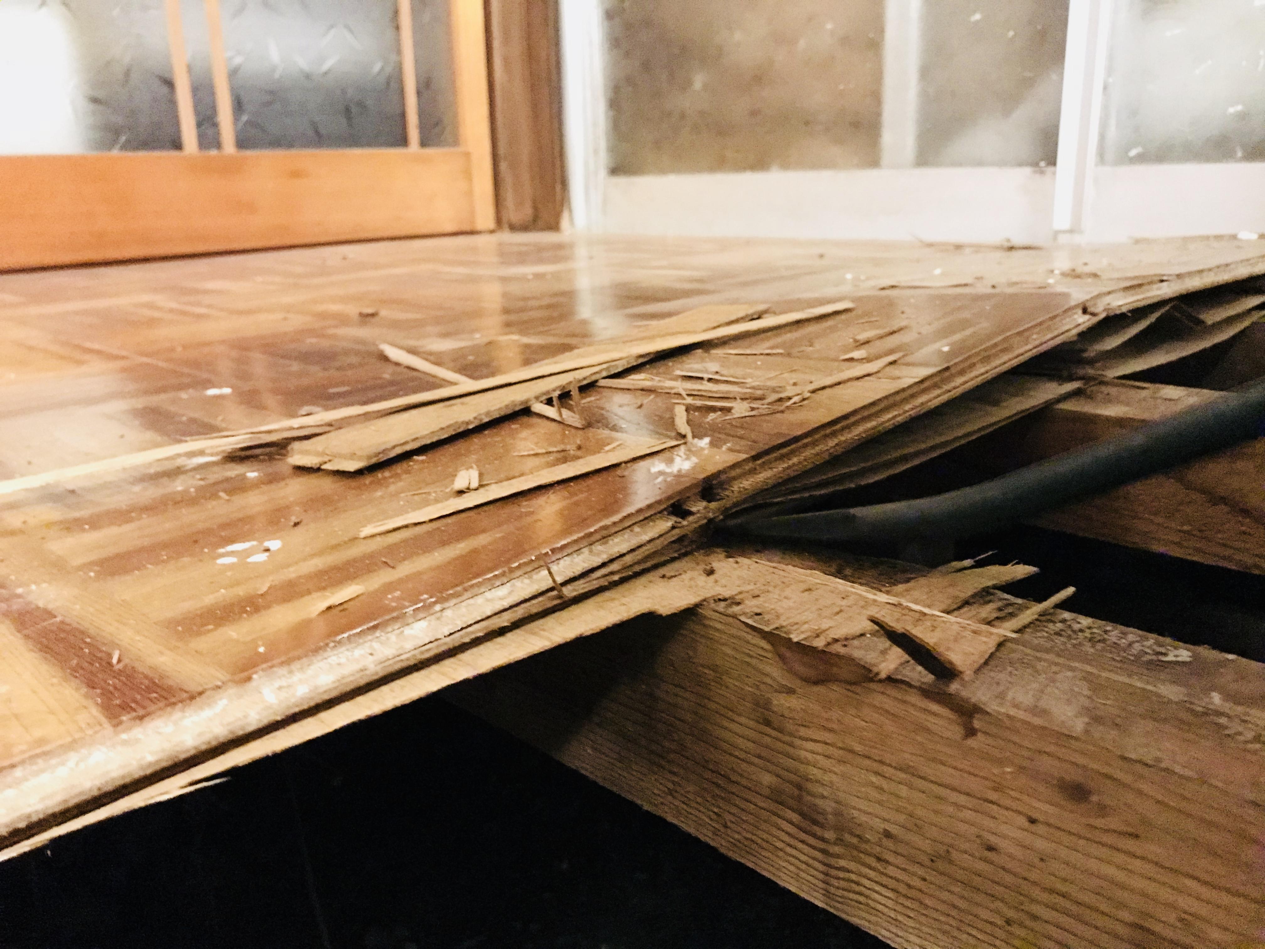 バールで床を剥がす